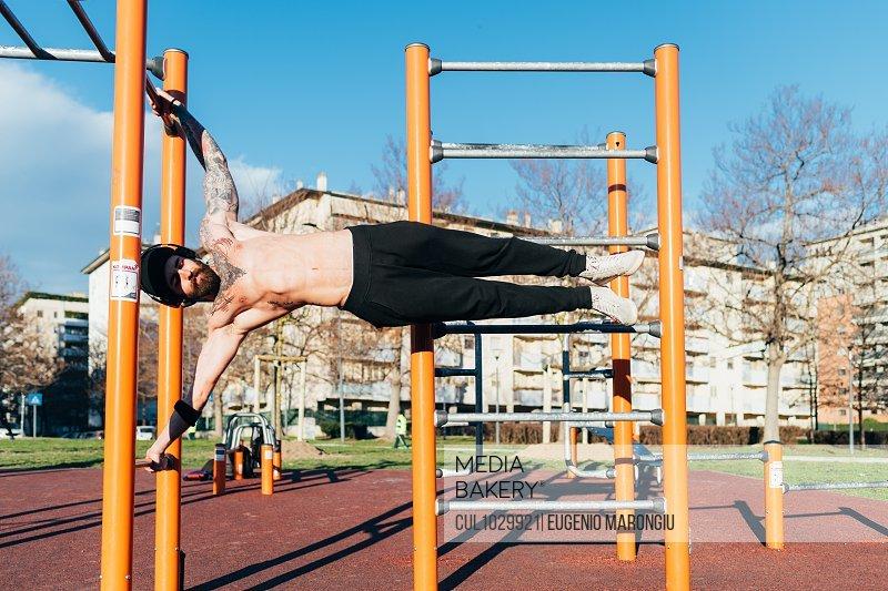 Man using horizontal ladder in outdoor gym
