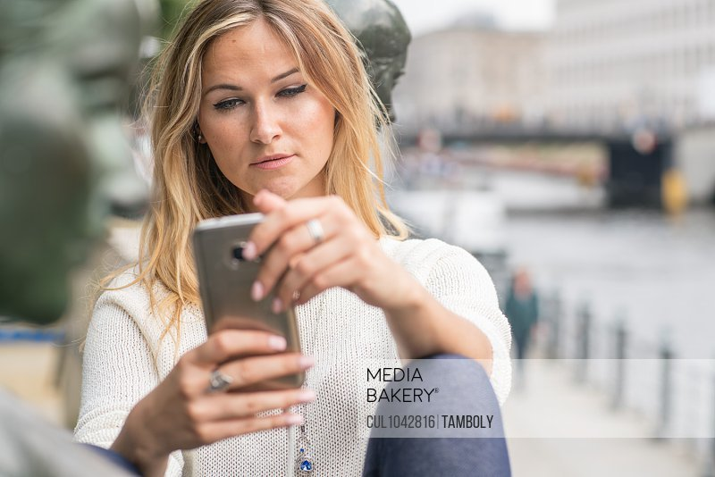 Smiling blond woman using smartphone with headphones in Berlin, Germany.