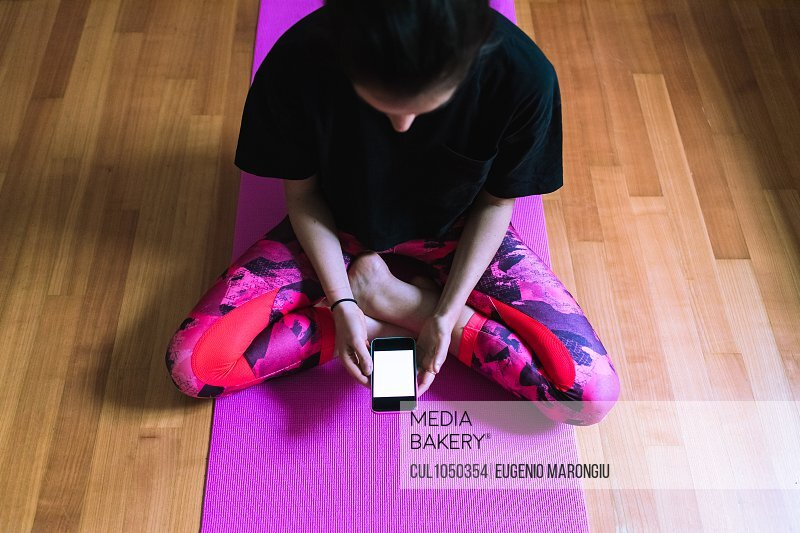 Young woman sitting on yoga mat with mobile phone