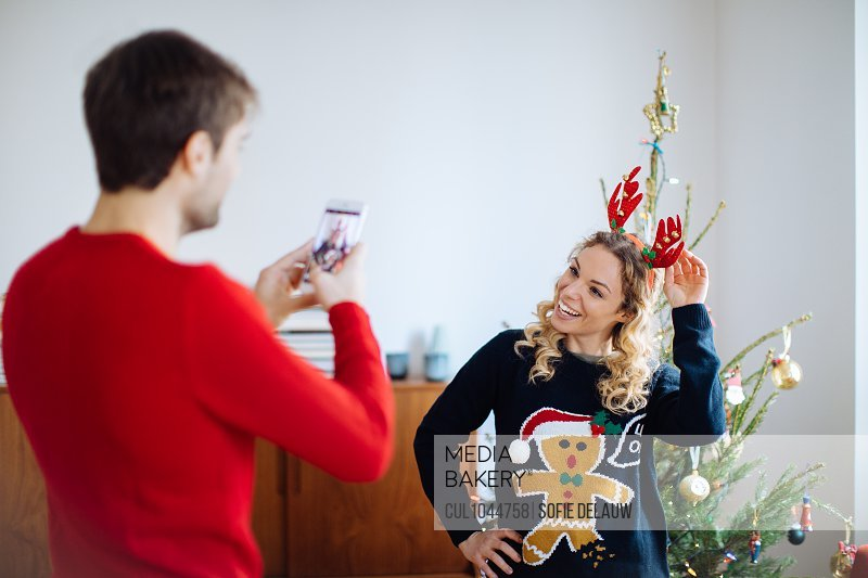 Man taking photograph of woman in front of Christmas tree at home