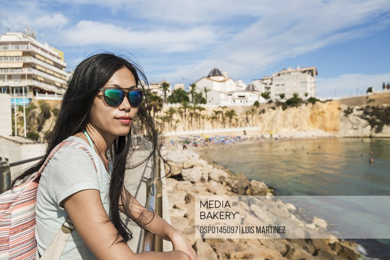 A Chinese young woman in sunglasses stands at a railing looking out at the water; Benidorm, Alicante, Spain