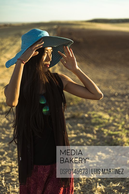 A young Asian woman walking in a golden wheat field; Madrid, Spain