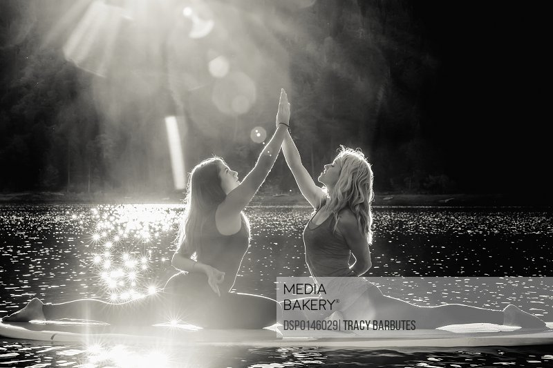 Fitness models doing yoga on a paddleboard on Pinecrest Lake; California, United States of America
