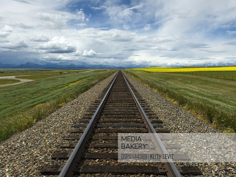 Train tracks between farm fields under a cloudy sky with Canadian Rockies in the distance; Alberta, Canada