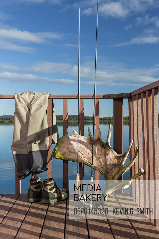 Fly fishing poles, boots, and waders rest against a railing with a shed moose antler on the deck of a building at the Tikchik Narrows Lodge, Tikchik Lake in the background on a clear summer day, Wood Tikchik State Park, Southwestern Alaska; Alaska, United States of America