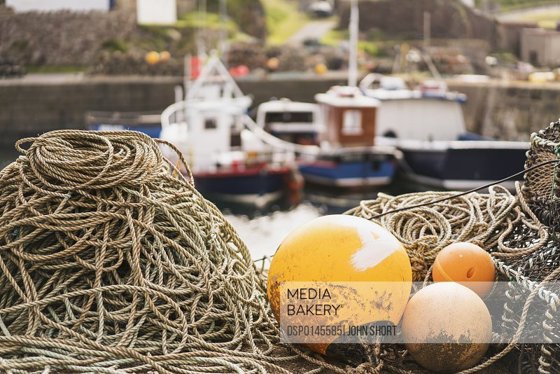 Buoys sitting on rope with fishing boats moored in the background; St. Abbs Head, Scottish Borders, Scotland