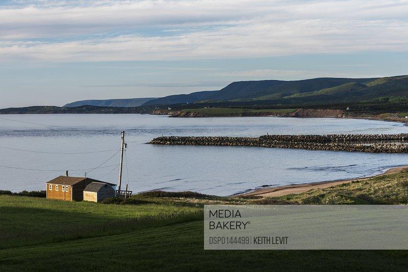 A house and breakwater along the Atlantic coastline, Cape Breton Island; Margaree, Nova Scotia, Canada