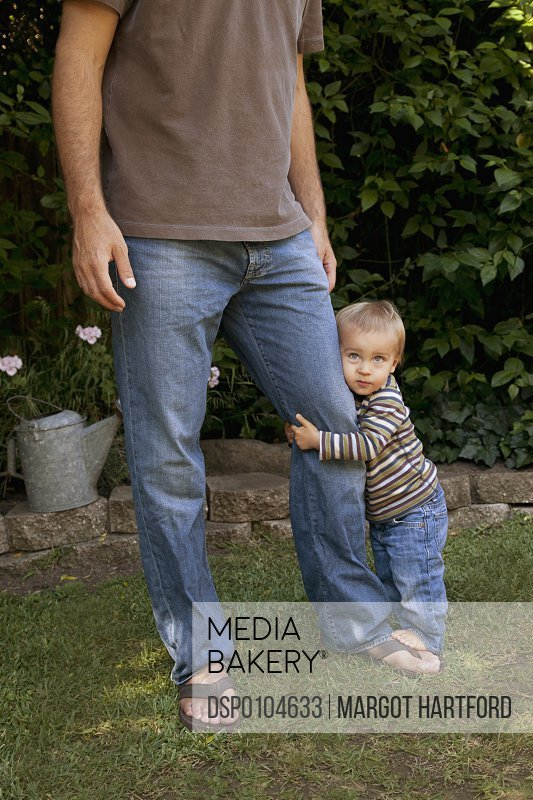 A Young Boys Holds Onto His Father S Leg Pacifica California United States Of