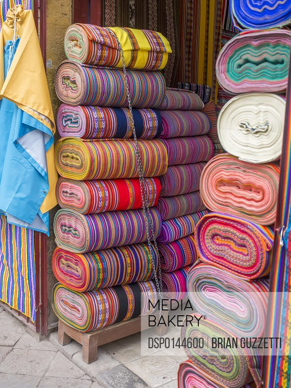 Bolts of colourful Peruvian designs in a street market, these patterns are part of the indigenous Quechua culture; Cusco, Peru