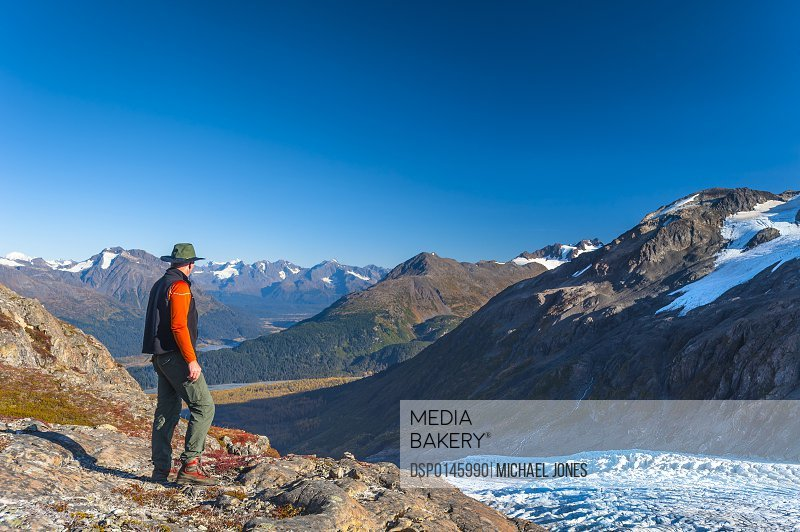 A man hiking near an unnamed lake near the Harding Icefield Trail in Kenai Fjords National Park on a summer day, South-central Alaska; Alaska, United States of America