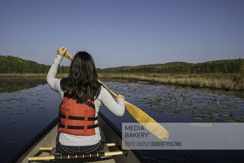 Woman canoeing in Algonquin Park; Ontario, Canada