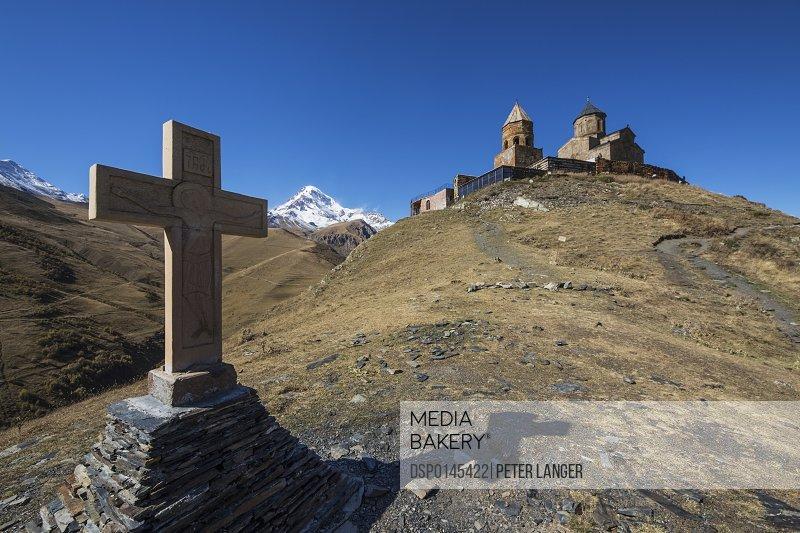 Stone cross and Gergeti Trinity Church with Mount Kazbek in the background; Kazbegi, Mtskheta-Mtianeti, Georgia