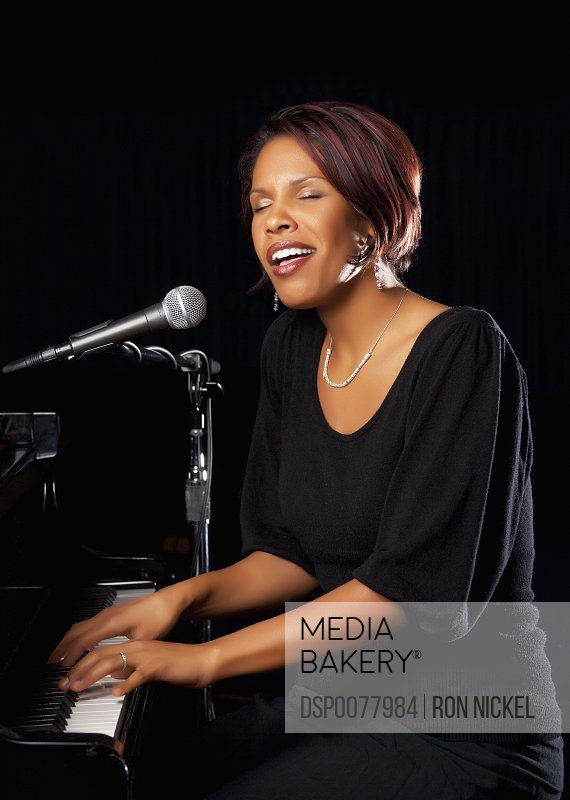 Fort Lauderdale, Florida, United States Of America A Woman Playing The Piano And Singing Into A Microphone