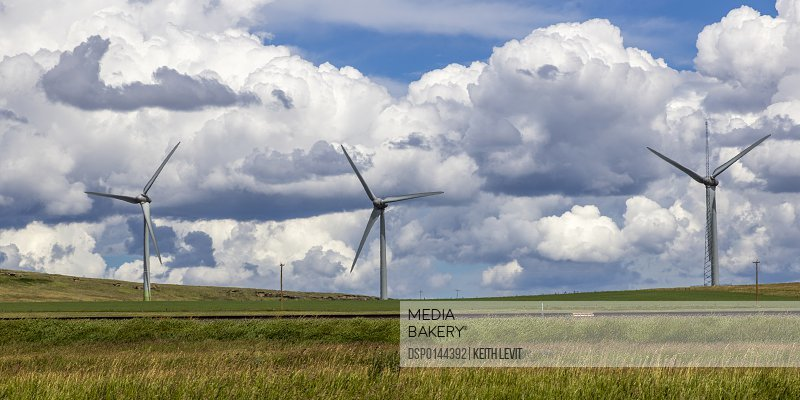 Wind turbines on a field with train tracks, with cloud; Pincher Creek, Alberta, Canada