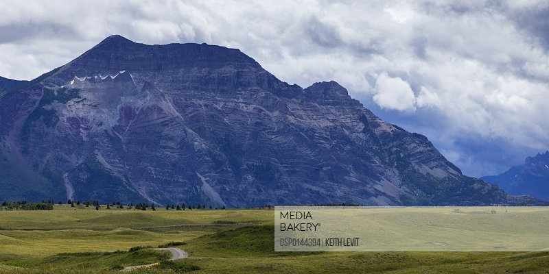 Rugged mountain under a cloudy sky at the edge of the foothills; Waterton, Alberta, Canada