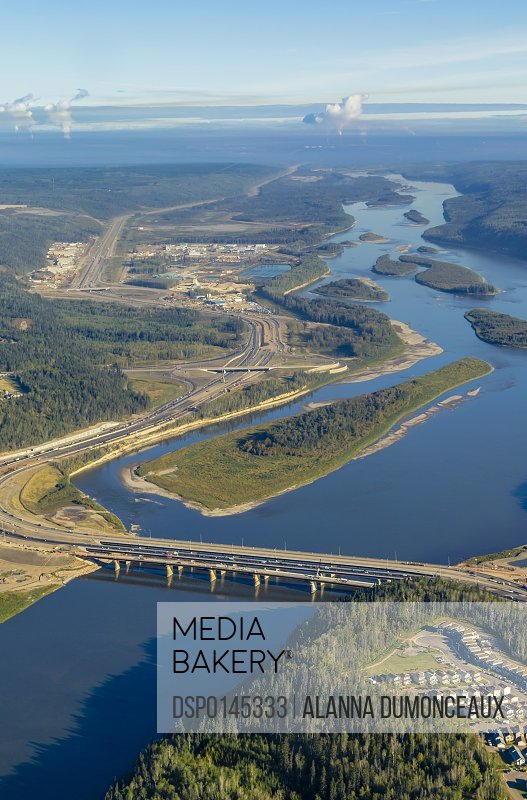 This aerial view shows the city of Fort McMurray Alberta and the Athabasca River with the oil sands regional production mines viewed in the far distance of the river; Fort McMurray, Alberta, Canada