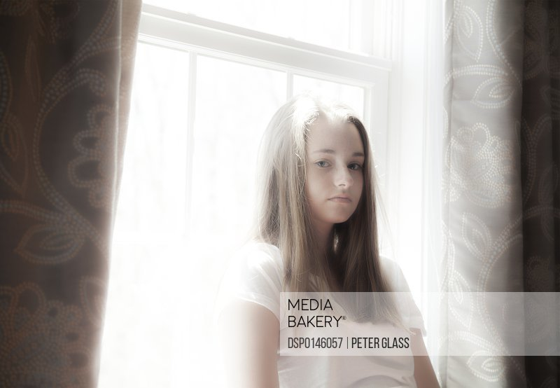 Portrait of a teenage girl in front of a window; Connecticut, United States of America
