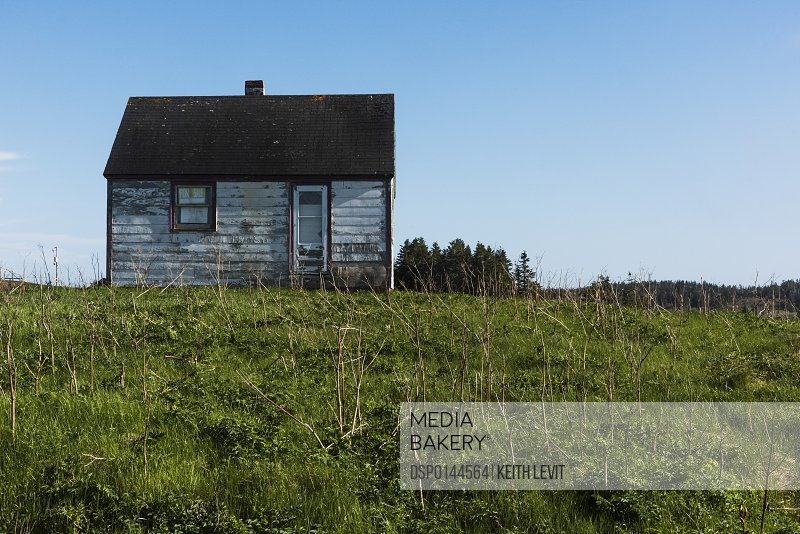 Small weathered wooden house surrounded by grass on Cape Breton Island; Nova Scotia, Canada