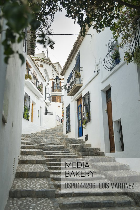 Steps up a sloped street in the beautiful town of Altea in Costa Blanca, where the houses are painted with the typical Mediterranean colours, white walls and blue doors and windows; Altea, Alicante, Spain