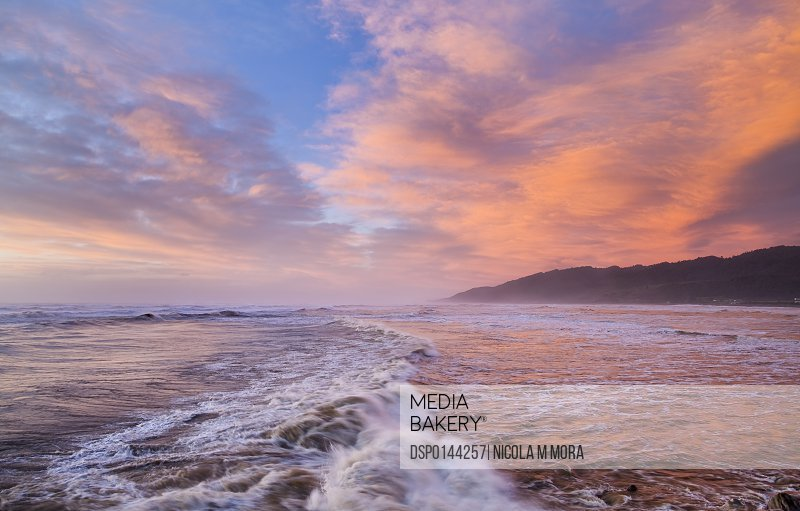 Vibrant red sunset over Cobden beach and waves, sunset reflected in the sea; Greymouth, South Island, New Zealand