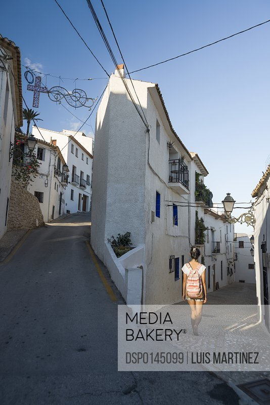 A Chinese young woman walking on the street of the beautiful town of Altea in Costa Blanca; Altea, Alicante, Spain