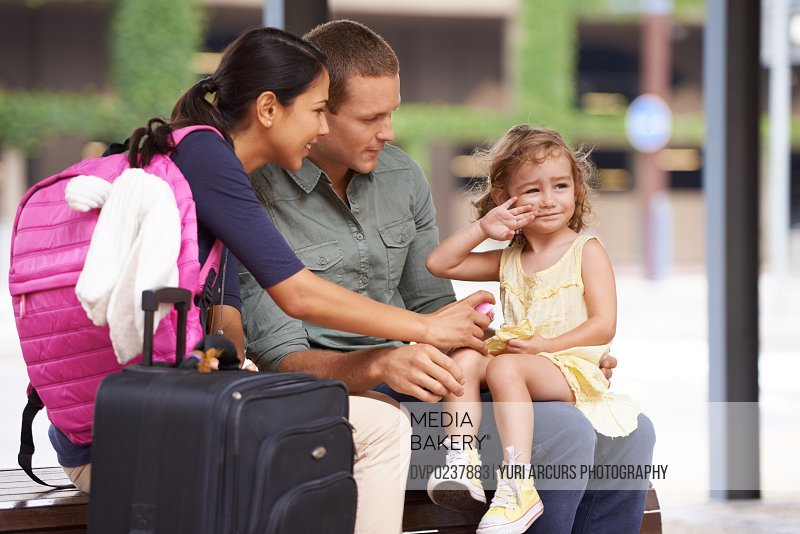 A cute little girl waves farewell as she goes on holiday with her parents