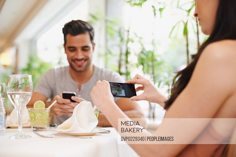 A woman taking a picture while dining out with her partner at a restaurant