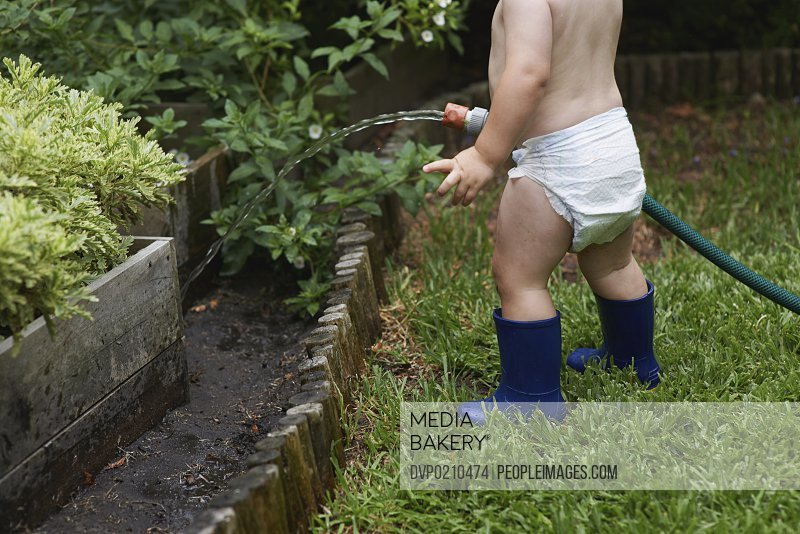 A young toddler watering the garden