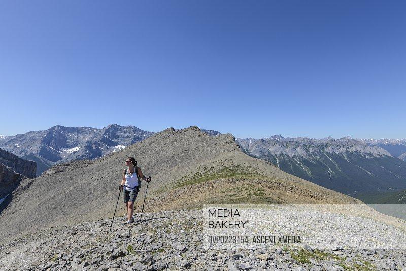 Woman walks along high ridge crest mtns below