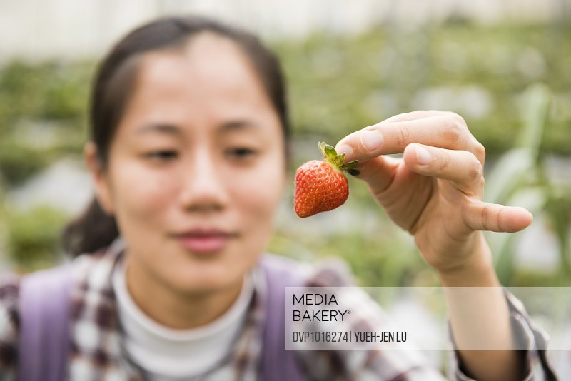 Young woman holding red strawberry