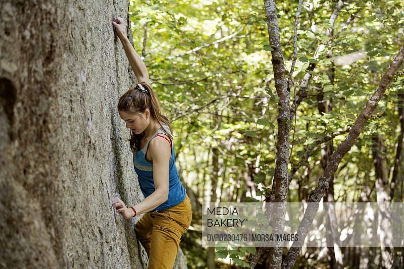Young woman climbing rock