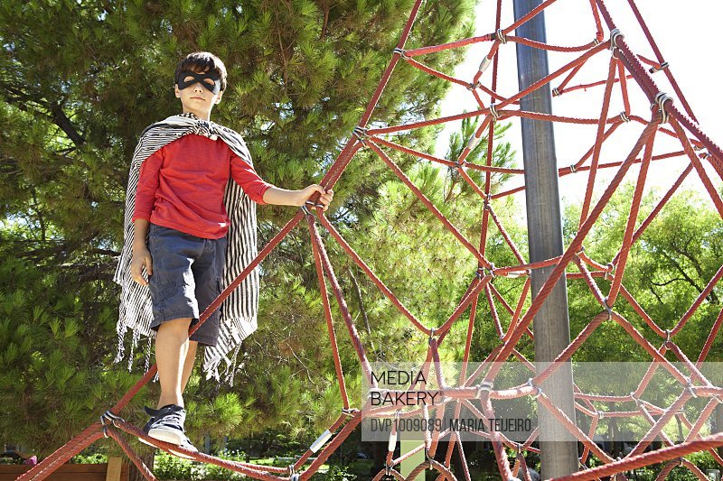 Boy child superhero climbing rope frame