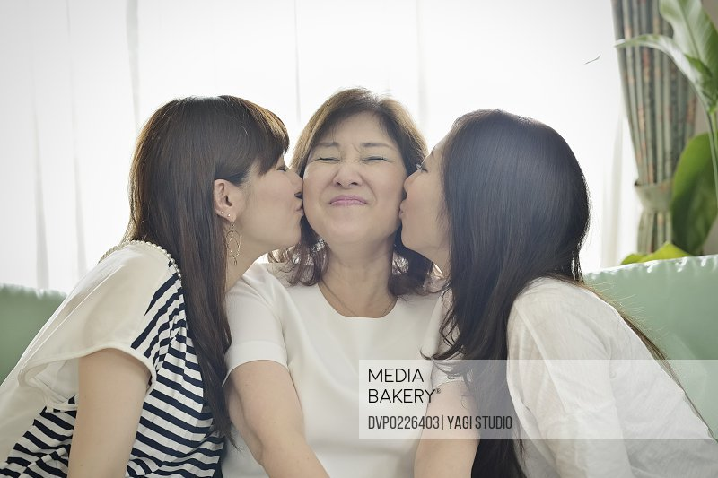 Two daughters?kissing mother