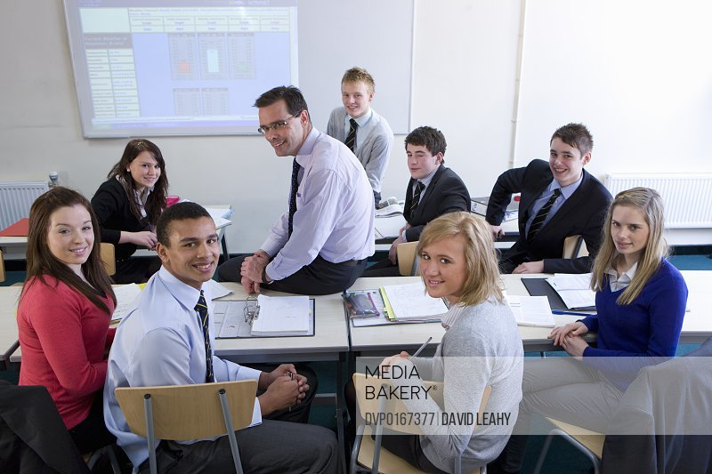 Teacher with his class all smiling to camera