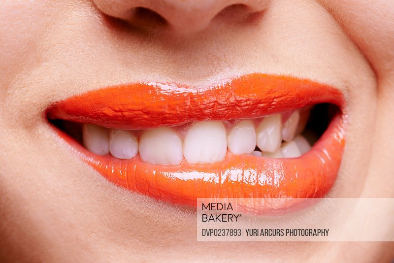 Cropped shot of a woman biting her orange colored lips