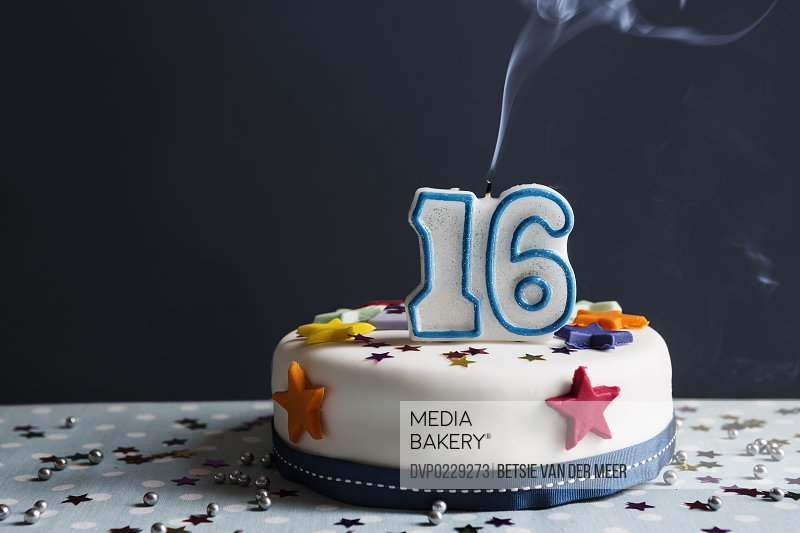 Still life of birthday cake with Number 16 candle