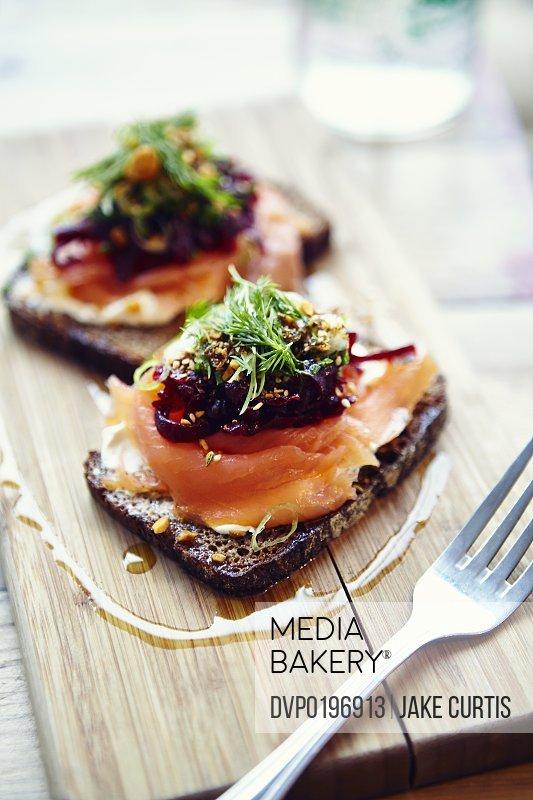 salmon tartine on rye bread on wooden board