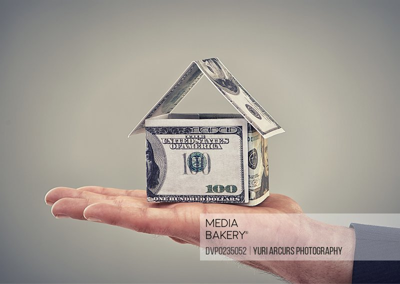 Close up conceptual shot of a man holding money that has been made to look like a house