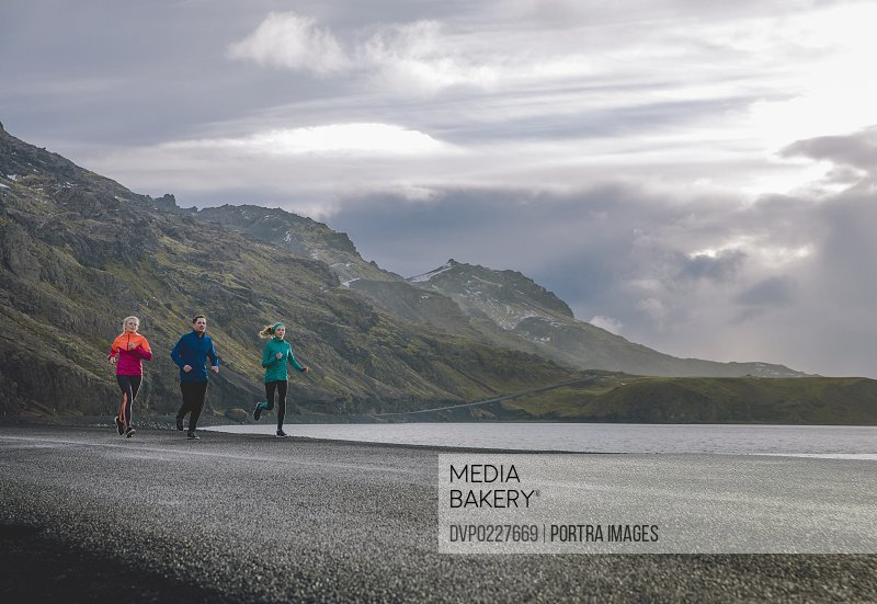Full length of male and female friends running on road by lake against mountain