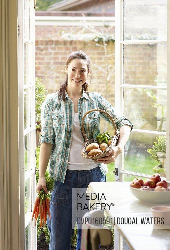 Woman holding fresh vegetables.