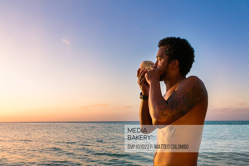 Local fijian man blowing traditional conch shell at sunset, Fiji, Pacific Islands