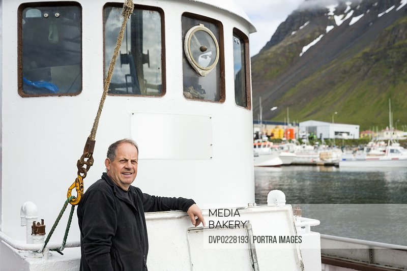 Portrait of confident fisherman leaning on fishing boat at harbor