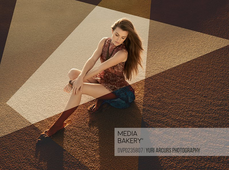 Stylized image of a beautiful young woman sitting on sand in brown tones