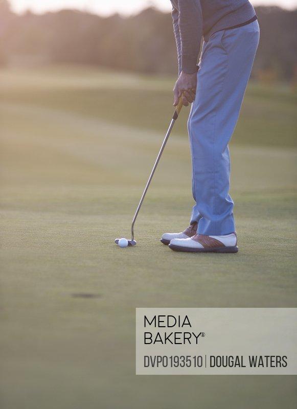 Male golfer preparing to putt ball on green