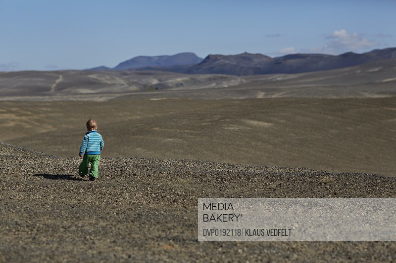Small child running in big mountain landscape