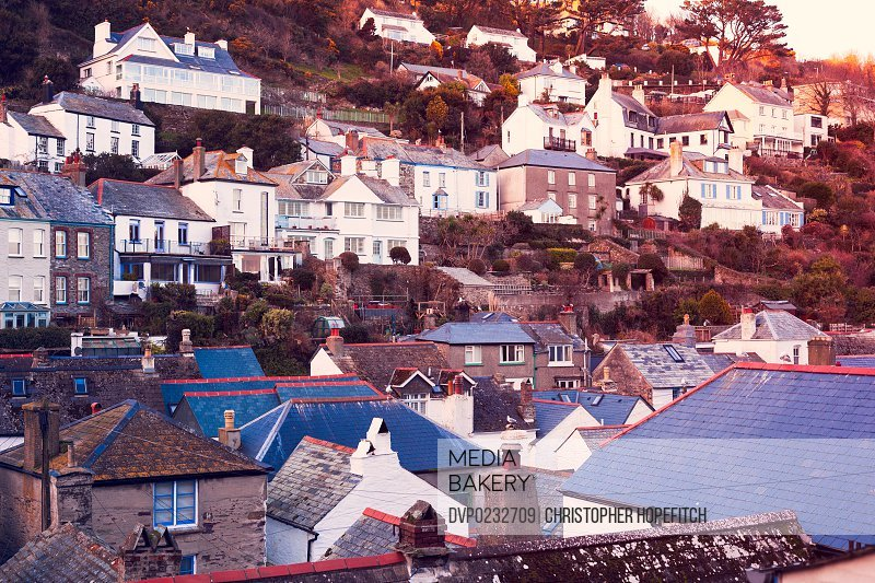 The sun setting over the slate rooftops of Polperro a small Cornish fishing village
