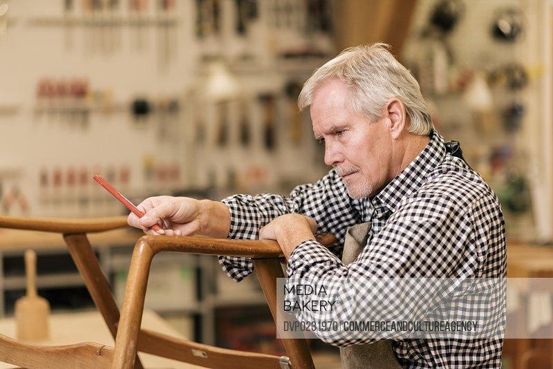 carpenter in wood workshop making chair