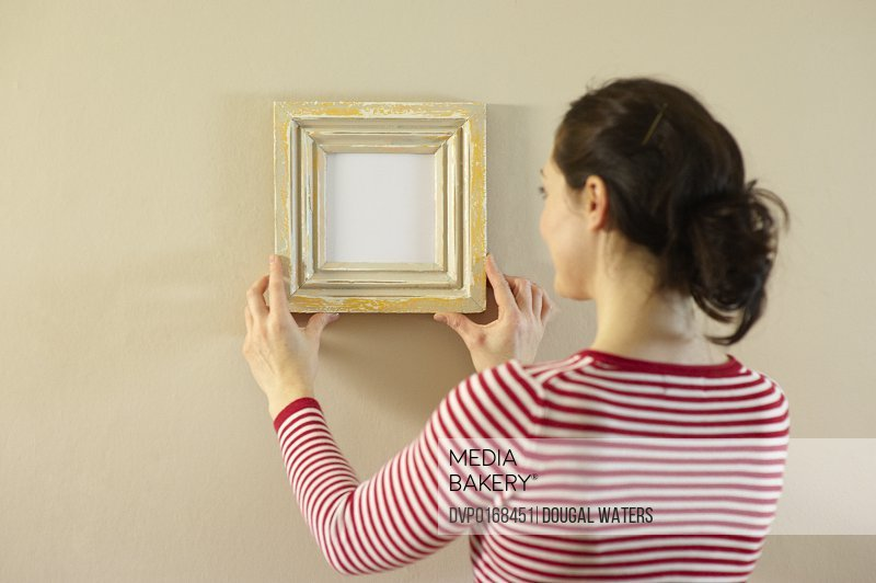 woman placing small picture frame on wall