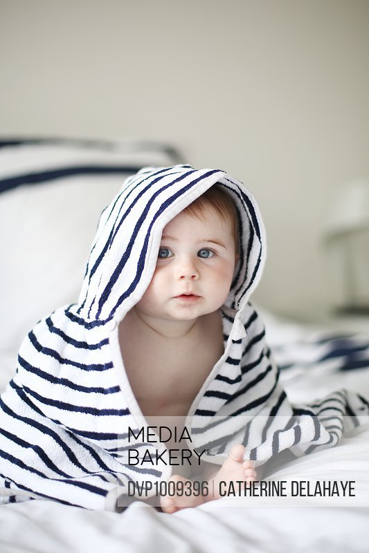 A 7 months old baby under a towel