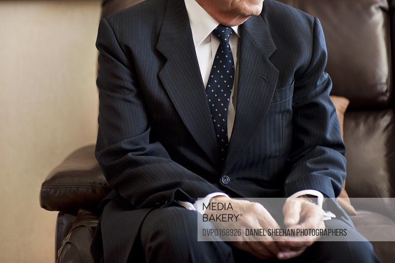 Man in suit sitting on leather chair